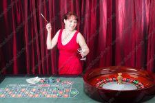 Смеющаяся молодая женщина играет в рулетку в казино